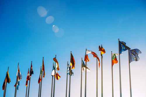 All European Union flags against blue sky in front of parliament